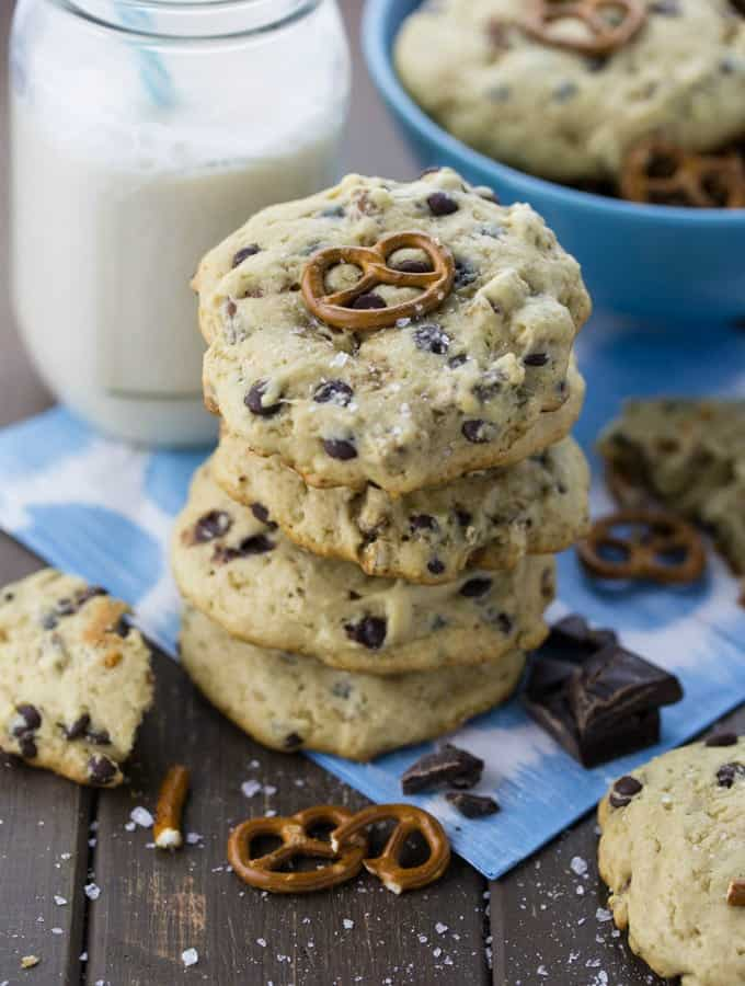 a stack of vegan chocolate chip pretzel cookies with a glass of milk and a bowl with more cookies in the background