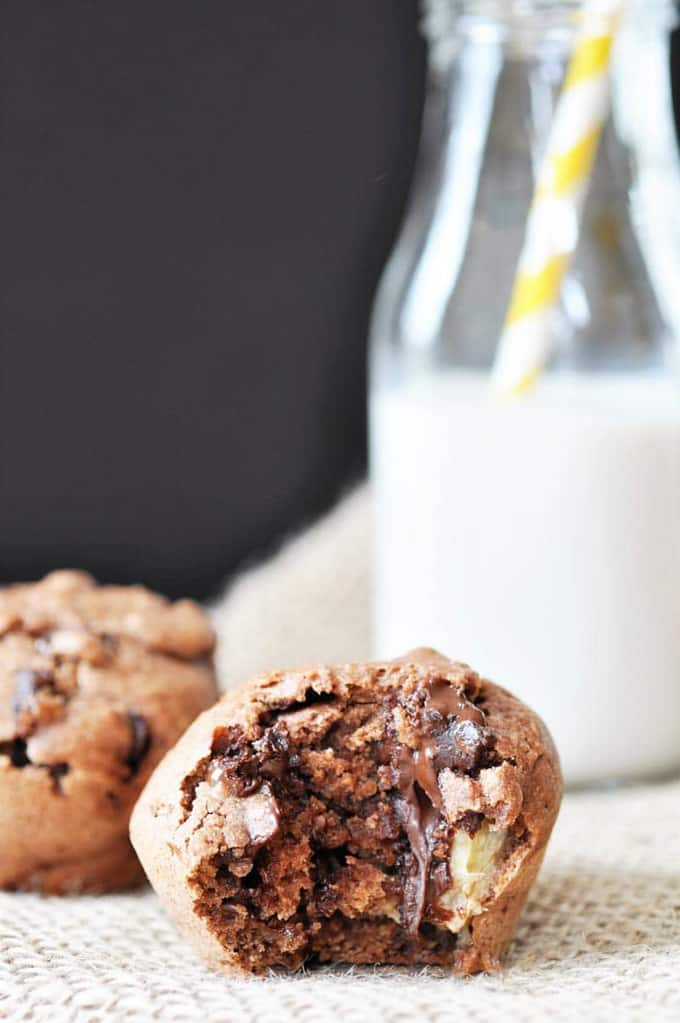 two vegan chocolate muffins with a bottle of milk and a yellow straw in the background