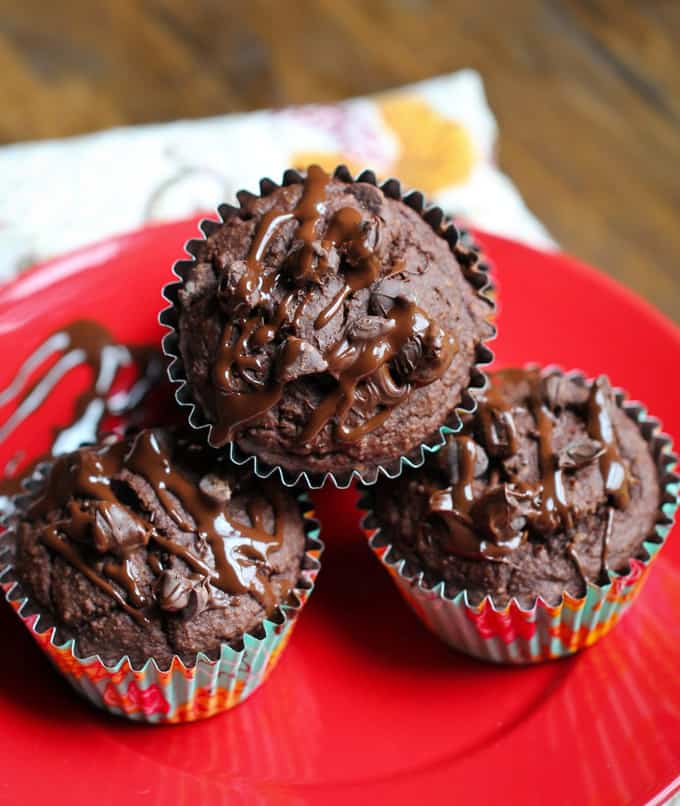 three vegan chocolate muffins on a red plate on a wooden board