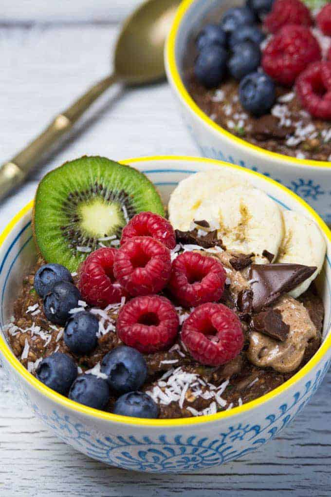 a bowl of vegan chocolate zucchini oats with fresh berries and bananas on top and another bowl in the background