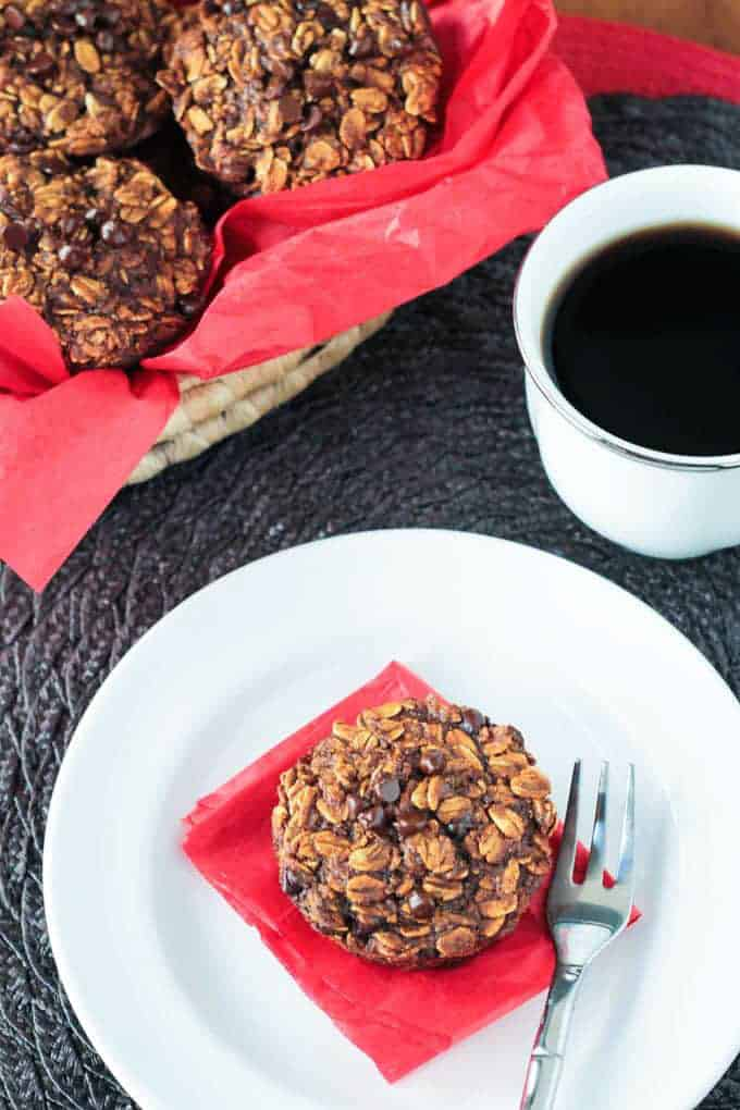 a gingerbread oatmeal cookie on a white plate with a red napkin with more cookies in the background and a cup of coffee on the side