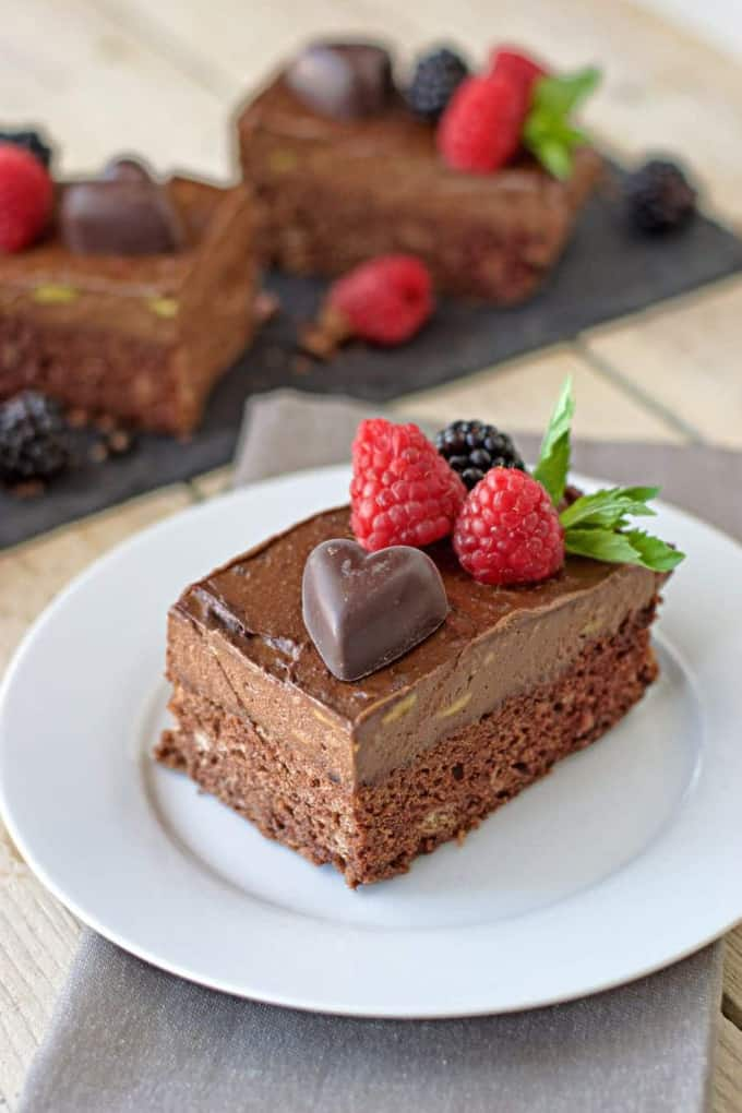 a piece of vegan chocolate mousse cake with berries on top on a white plate with two more pieces in the background