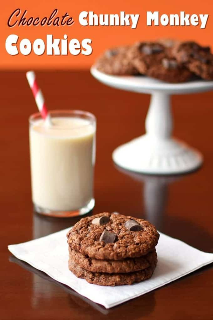 a stack of three vegan chunky monkey chocolate cookies on a white napkin with a glass of milk and more cookies in the background