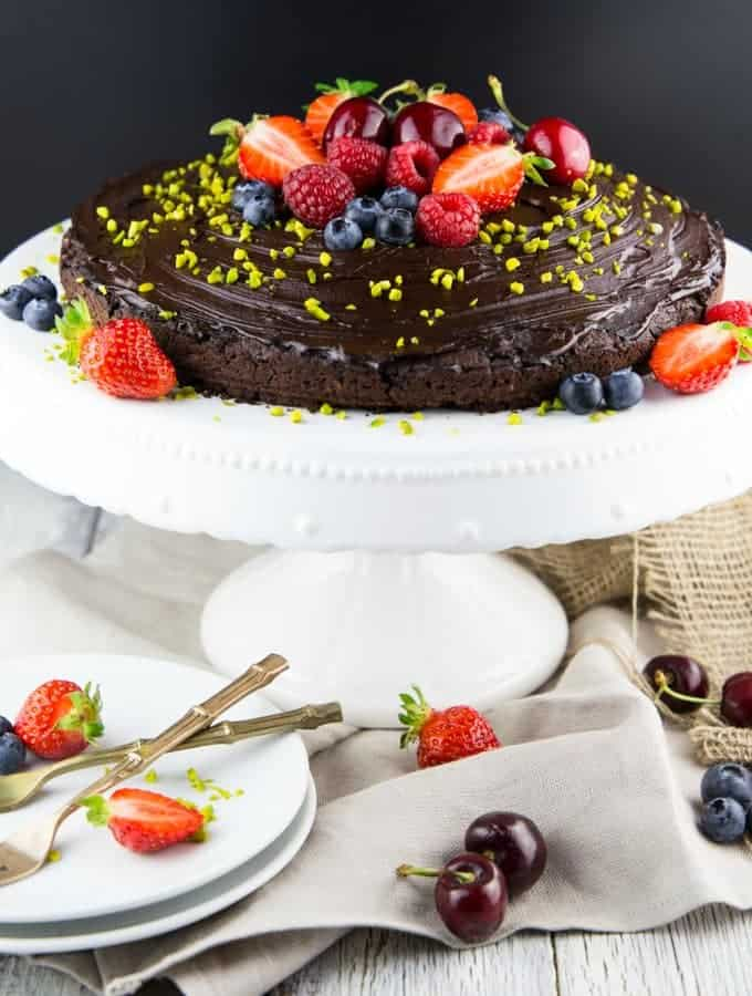 a vegan chocolate cake with fresh berries on top on a cake plate with two white plates and forks in front