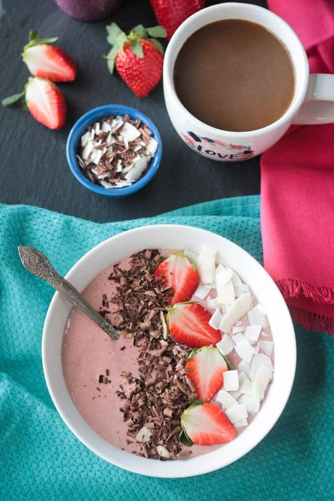 a chocolate strawberry smoothie bowl on a blue dish cloth with a mug of coffee and fresh strawberries in the background