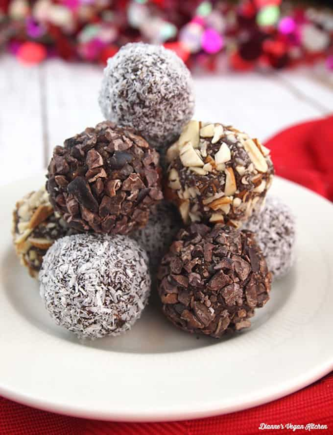 a stack of vegan chocolate truffles on a white plate on top of a red dish cloth