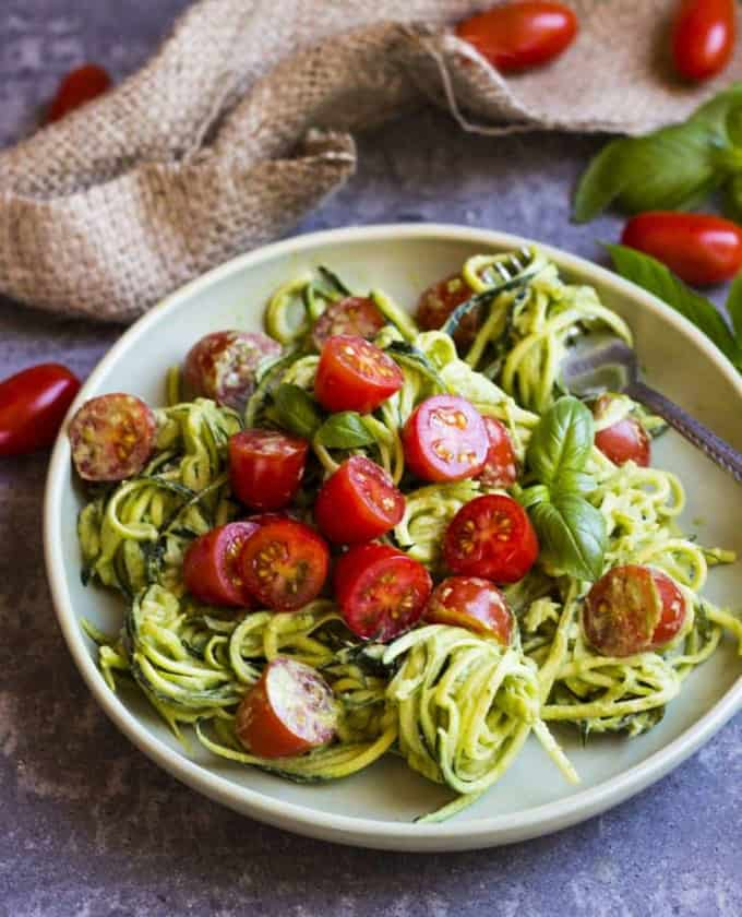 a plate with basil zoodles and cherry tomatoes on a grey counter top with basil leaves and tomatoes in the background