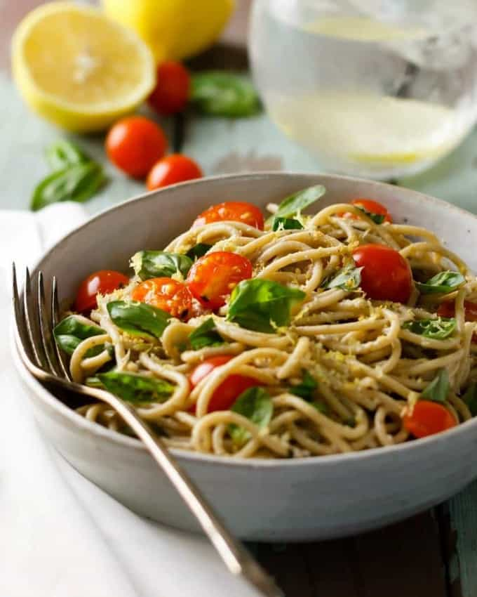 a bowl of lemon basil pasta with walnut parmesan and cherry tomatoes with a fork on the side and a glass of water and two lemons in the background