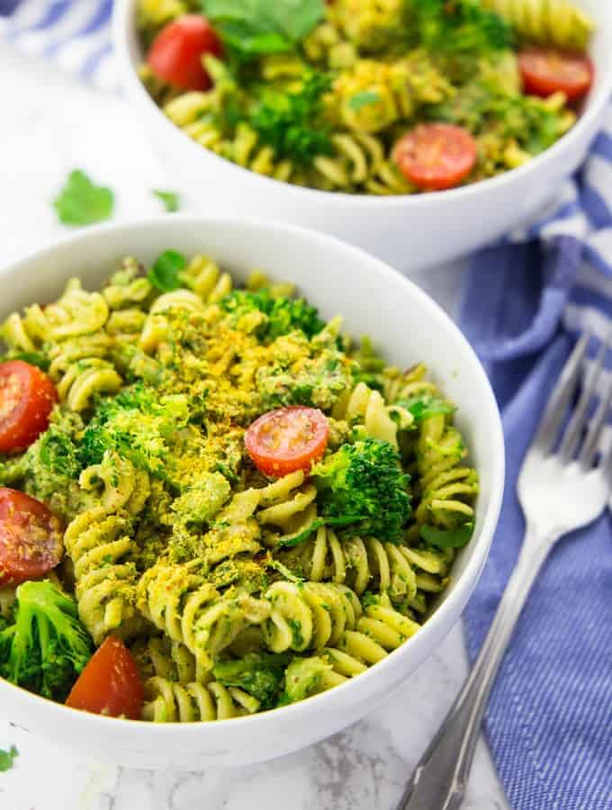 two bowls of vegan pasta with broccoli pesto and cherry tomatoes on a marble counter top with a blue dish cloth in the background