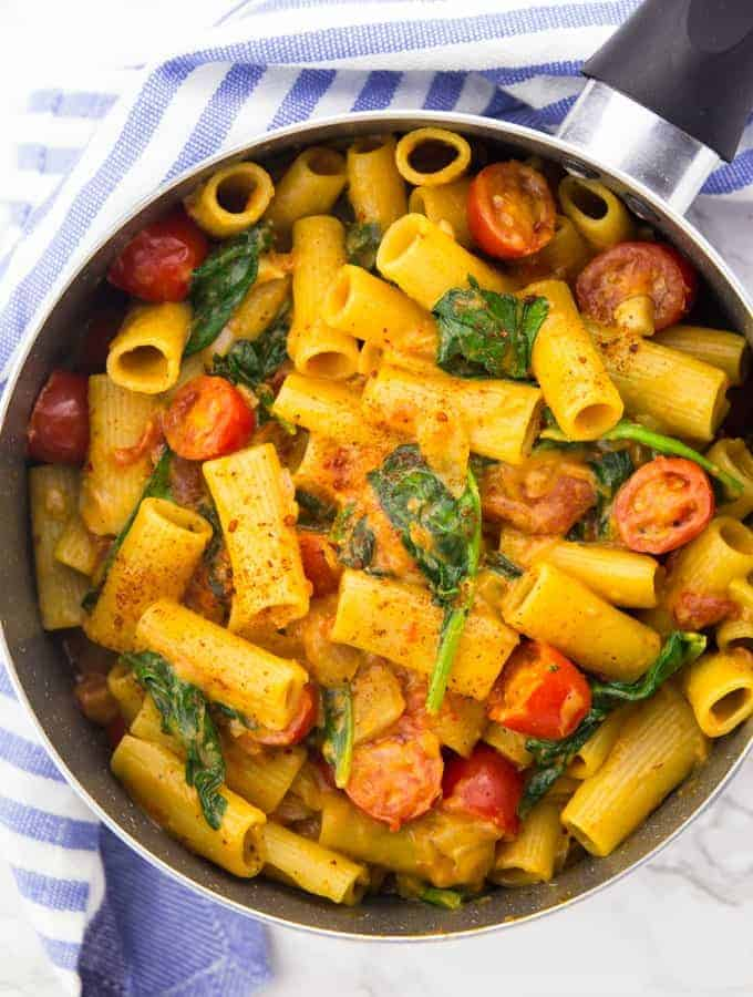 a pot of vegan one pot pasta with rigatoni, spinach, and cherry tomatoes on a marble counter top with a blue tablecloth