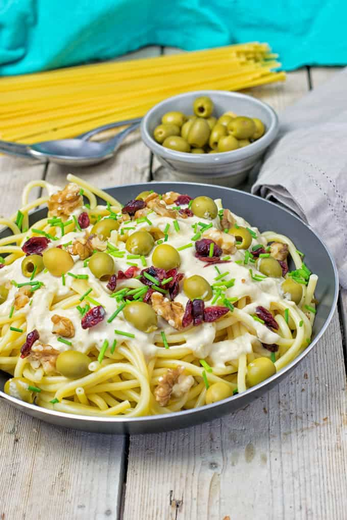 a bowl of mediteranean pasta with creamy sauce, green olives, and dried tomatoes in a grey plate with a small bowl of olives, a spoon, and uncooked spaghetti in the background
