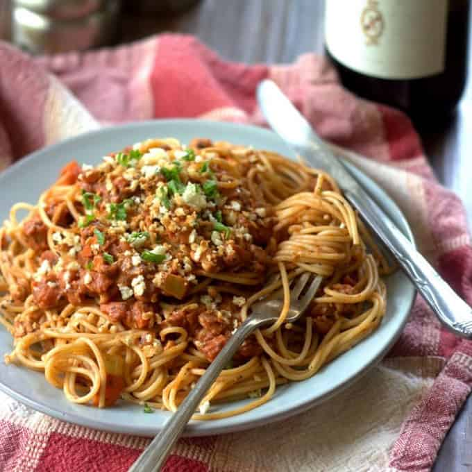 a plate of spaghetti with vegan tempeh ragu on top of a red and white tablecloth and a bottle of red wine in the background