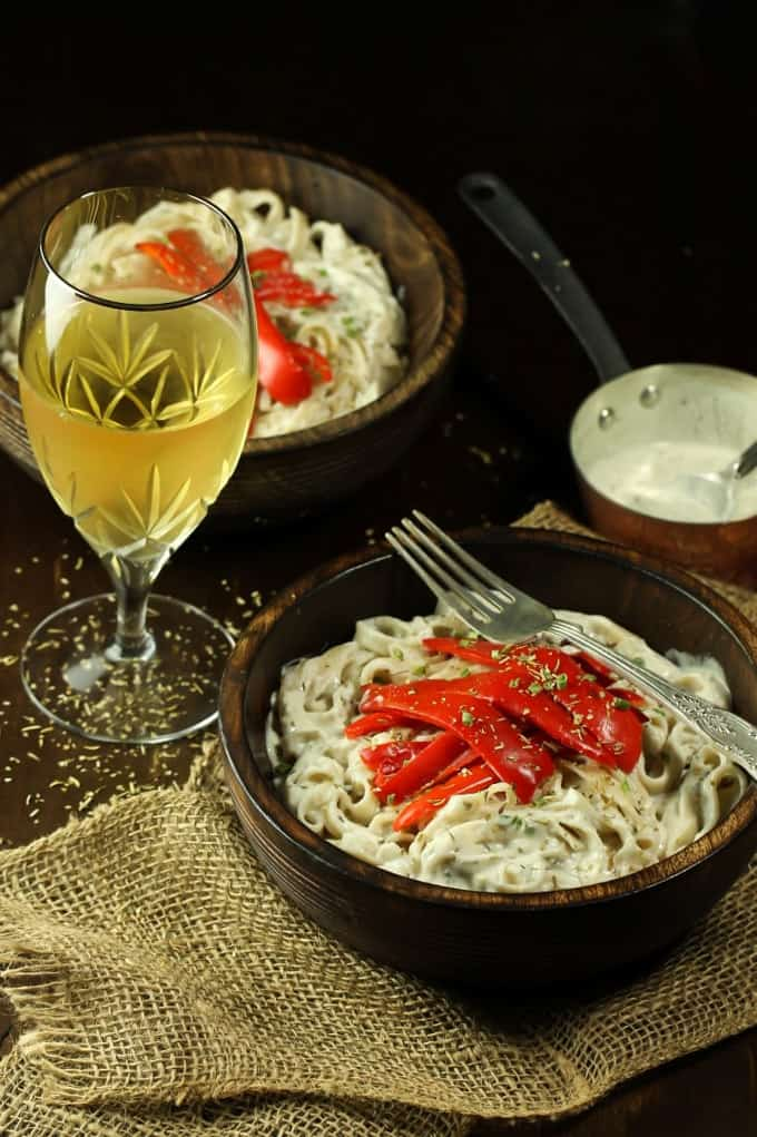 two bowls of creamy vegan white wine pasta with roasted red peppers on top and a glas of white wine on the side