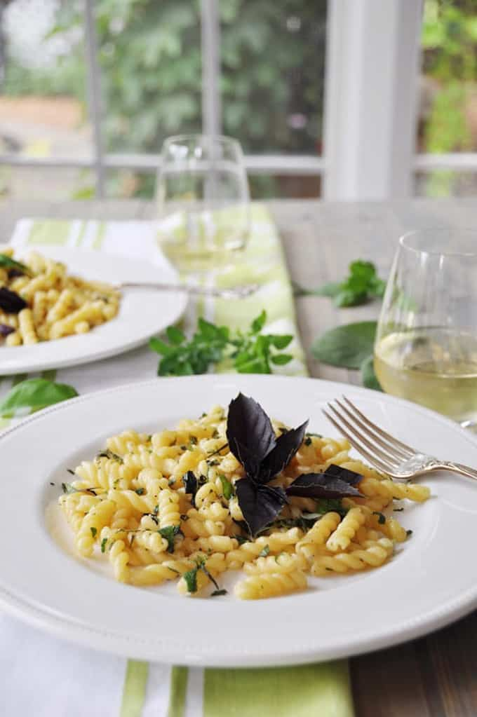two white plates with herb gemelli pasta on a table with two glasses of wine and a window in the background
