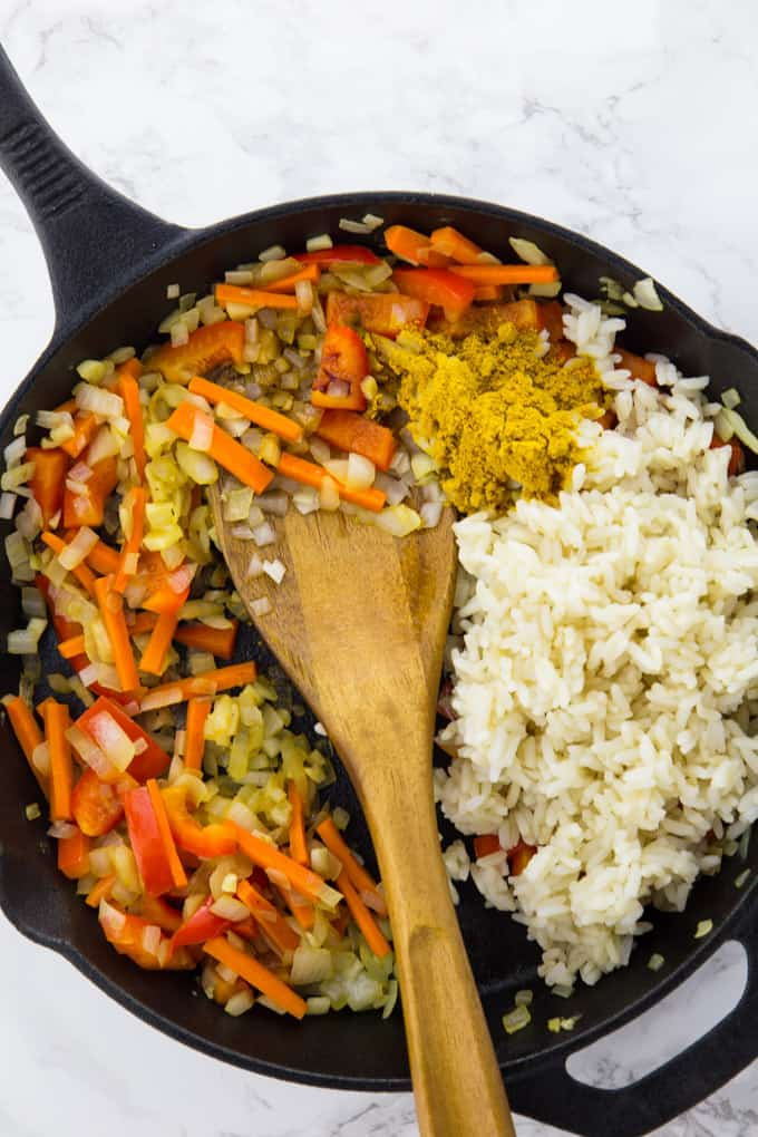 auted onions, carrots and red bell pepper, cooked rice, and curry powder in a cast iron skillet