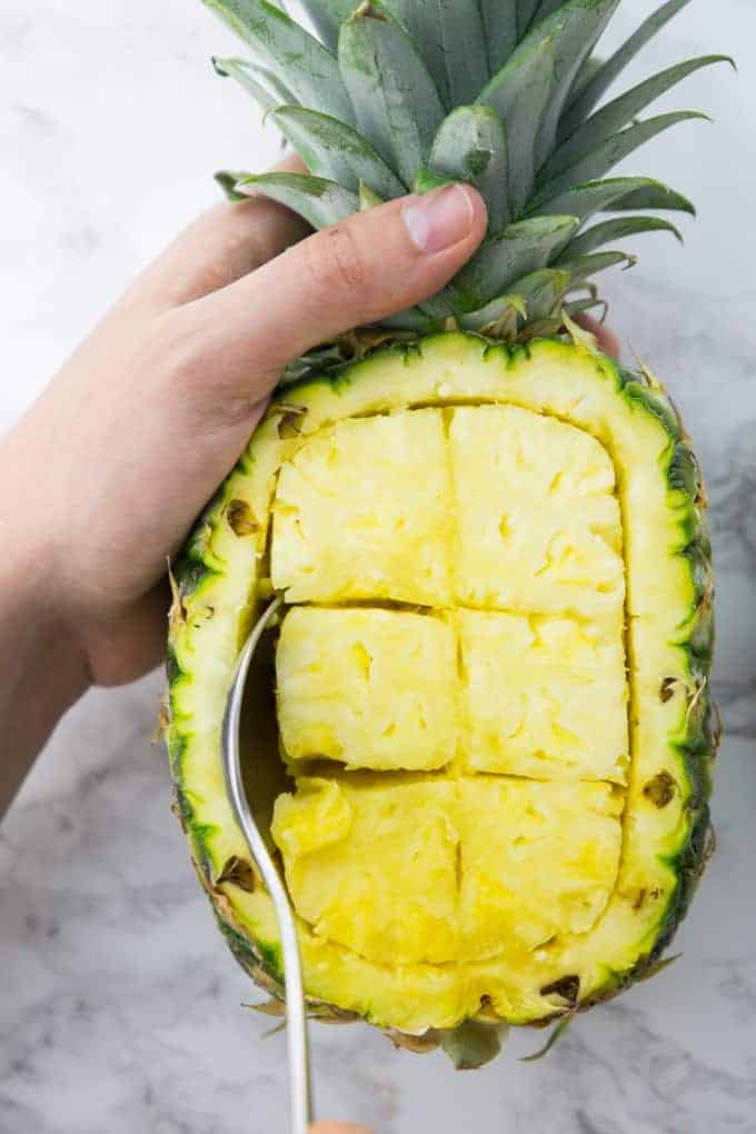 A Hand Spooning Pineapple Pieces out of a Pineapple to Make a Pineapple Bowl