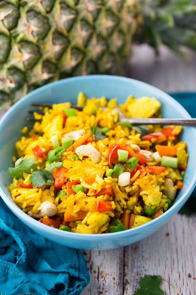 pineapple fried rice in a blue bowl with a fork with a pineapple in the background