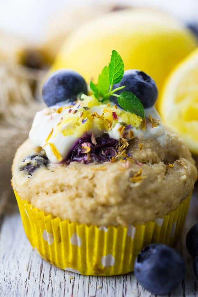 a close-up of a vegan blueberry muffins on a white wooden board with lemons in the background
