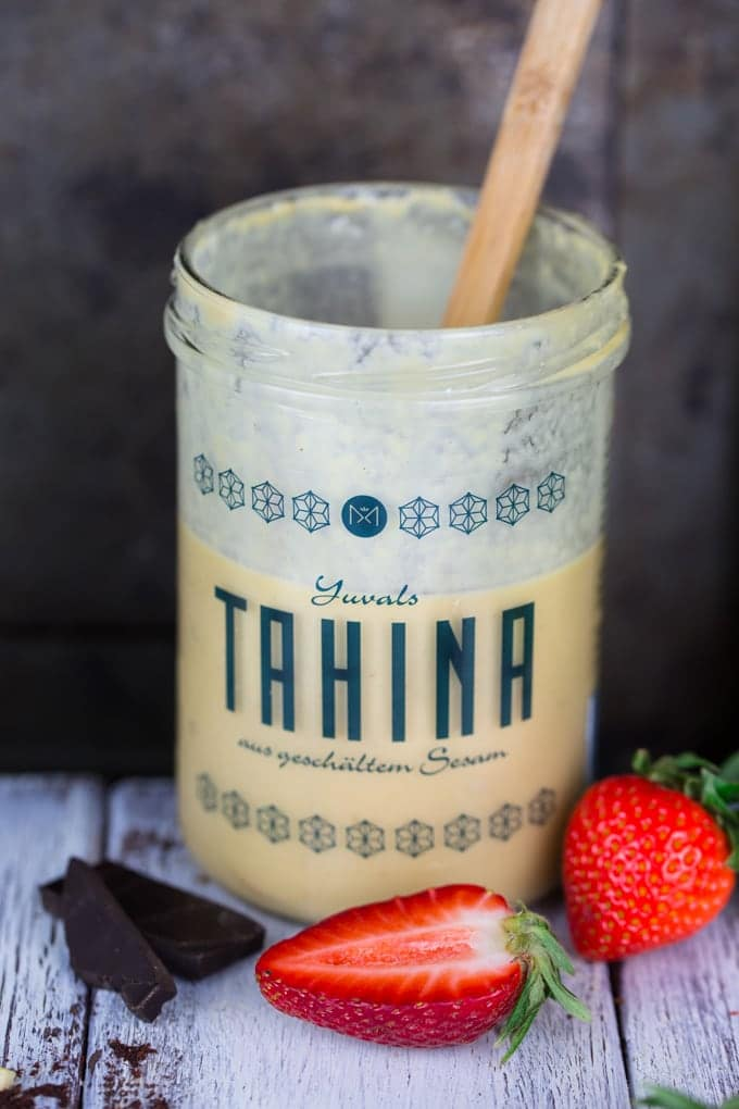 a jar of tahini with a wooden spoon on a white wooden countertop with dark chocolate and two strawberries on the side