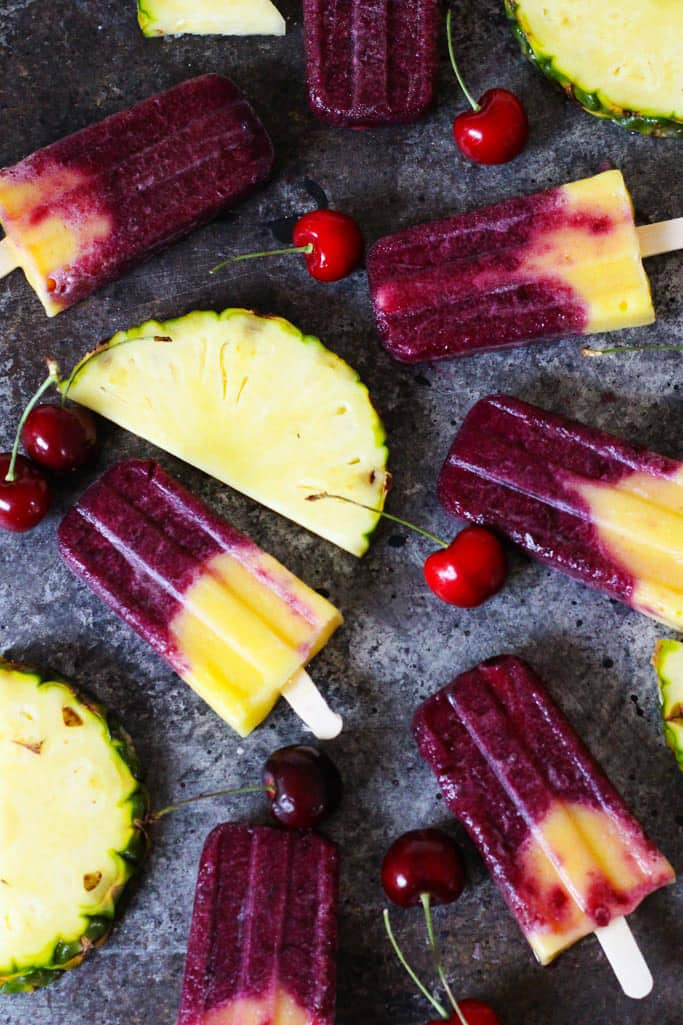 seven cherry and pineapple popsicles on a grey marble countertop with fresh cherries and pineapple slices on the side