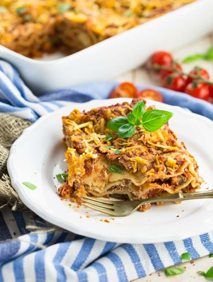 a piece of vegan lasagna on a white plate with a fork on the side and a casserole dish with more lasagna in the background