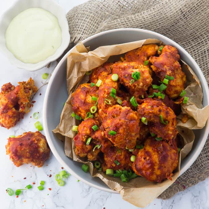a bowl of vegan cauliflower hot wings on a marble counter top with green onions on top