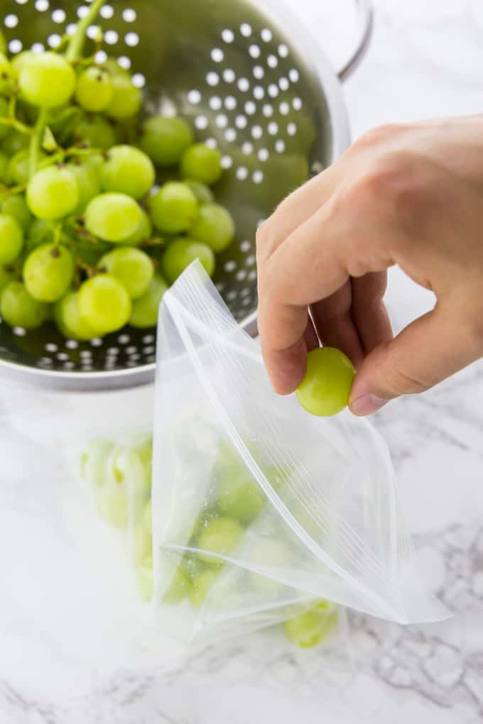 a hand filling white grapes in a ziploc bag with a colander with more grapes in the background