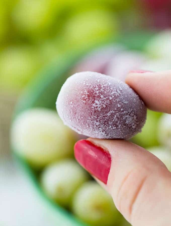 A hand holding a frozen grape with a bowl of more frozen grapes in the background
