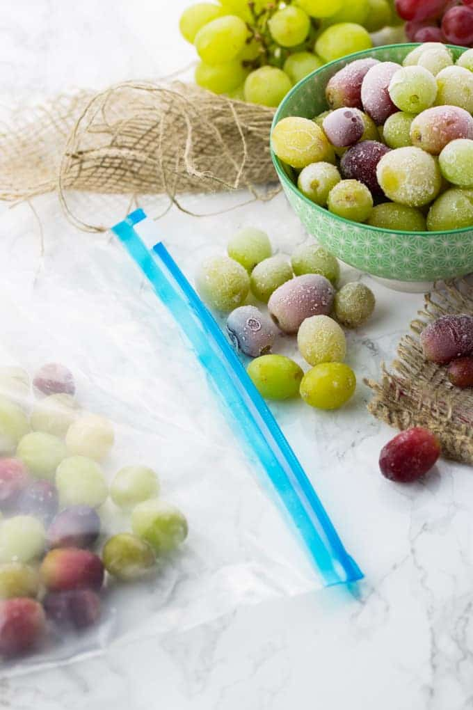 a bowl of frozen grapes on a marble counter top with a ziploc bag of frozen grapes on the side