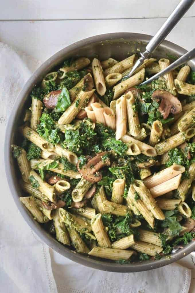 A pan full of penne with mushrooms and kale and two forks