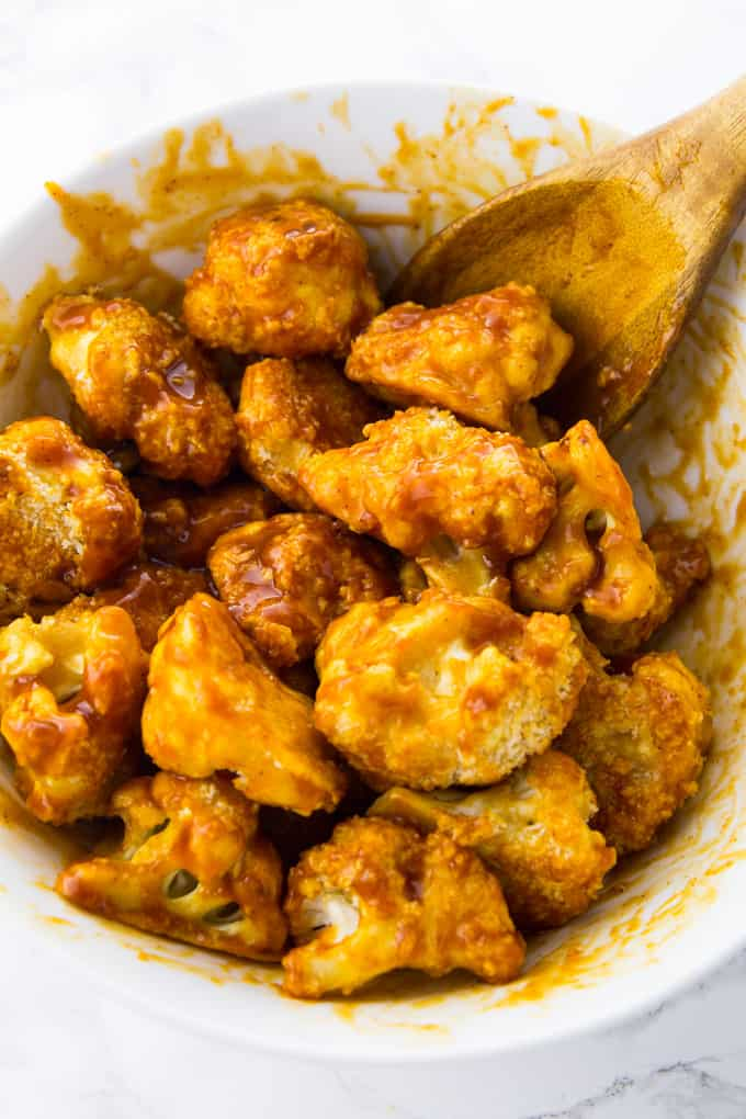 with BBQ sauce coated cauliflower wings in a bowl with a wooden spoon