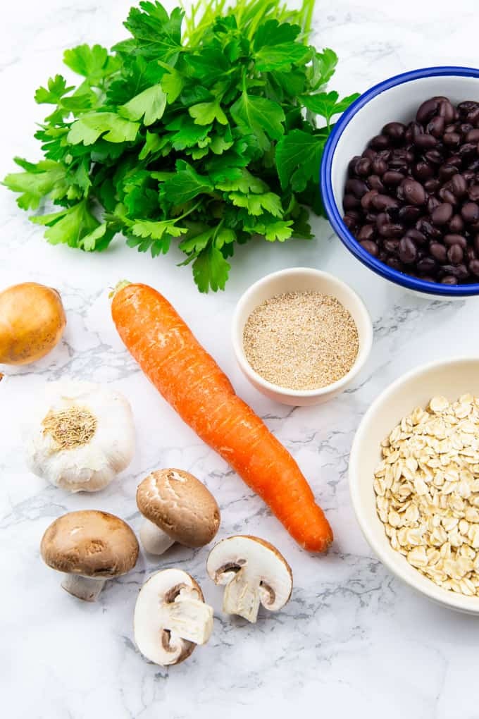 a bunch of parsley, a carrot, a few mushrooms, a bowl of black beans, and a bowl of rolled oats on a marble countertop