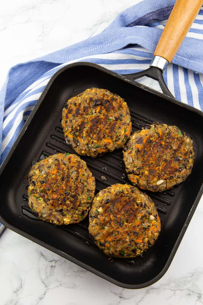 four vegan black bean burgers in a grill pan on a marble countertop