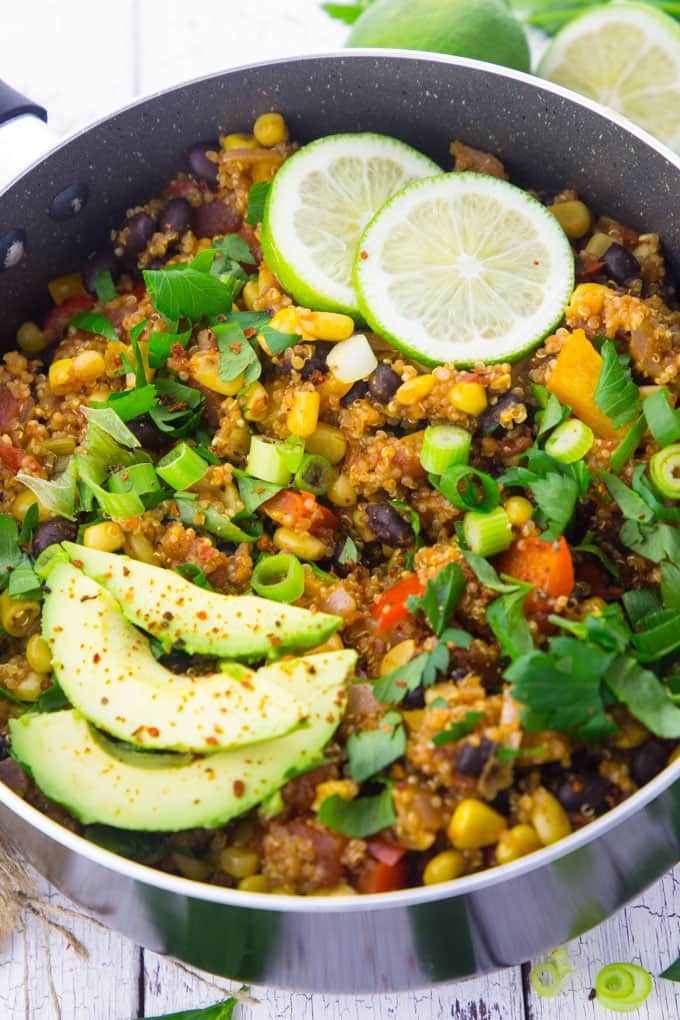 One pan Mexican quinoa in a black pot with avocado and lime slices on top