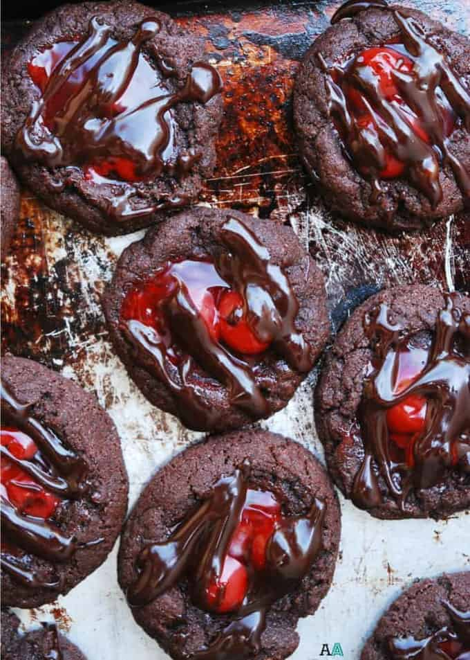 cherry chocolate thumbprint cookies on a baking sheet with extra chocolate drizzled on top