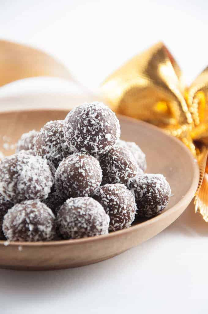 marzipan rum balls in a wooden bowl with a golden ribbon in the background
