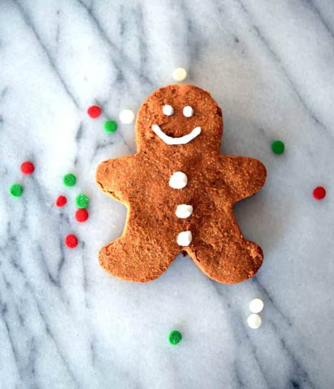 a vegan gingerbread man on a marble counter top with red, green, and white confetti on the side