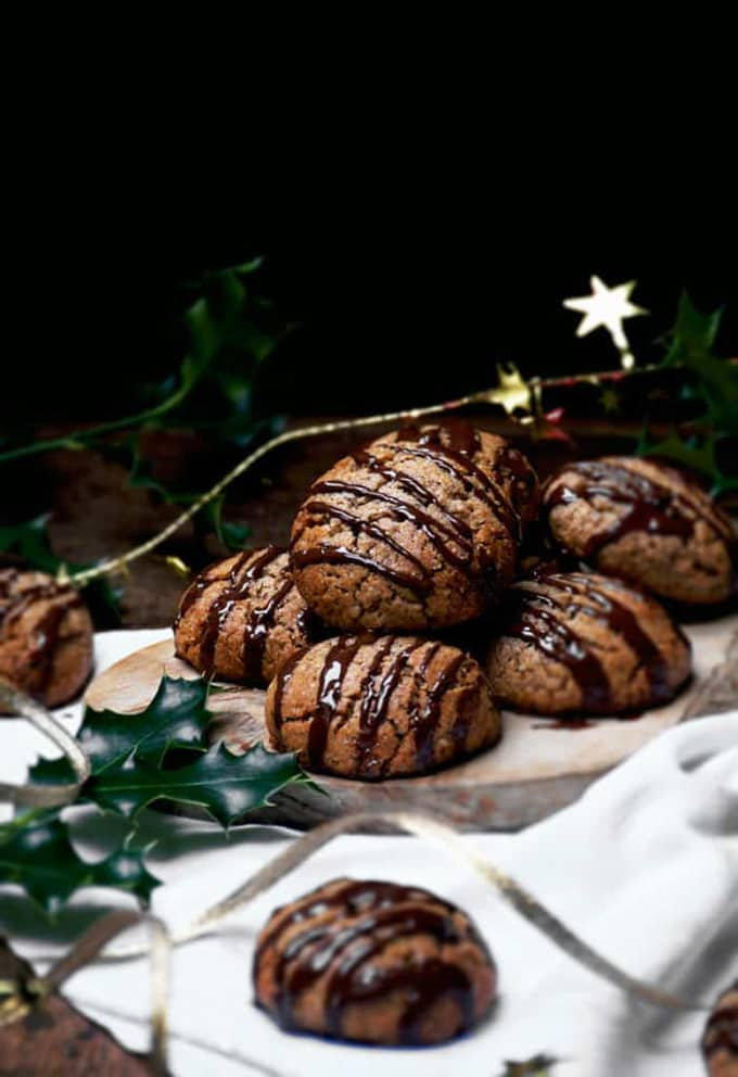 vegan lebkuchen drizzled with chocolate on a white dish cloth with Christmas decoration on the side and a black background