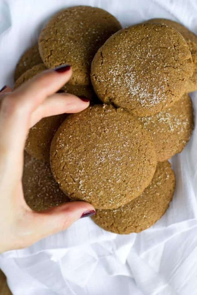 a hand holding a vegan ginger snap cookie over more cookies on a white dish cloth
