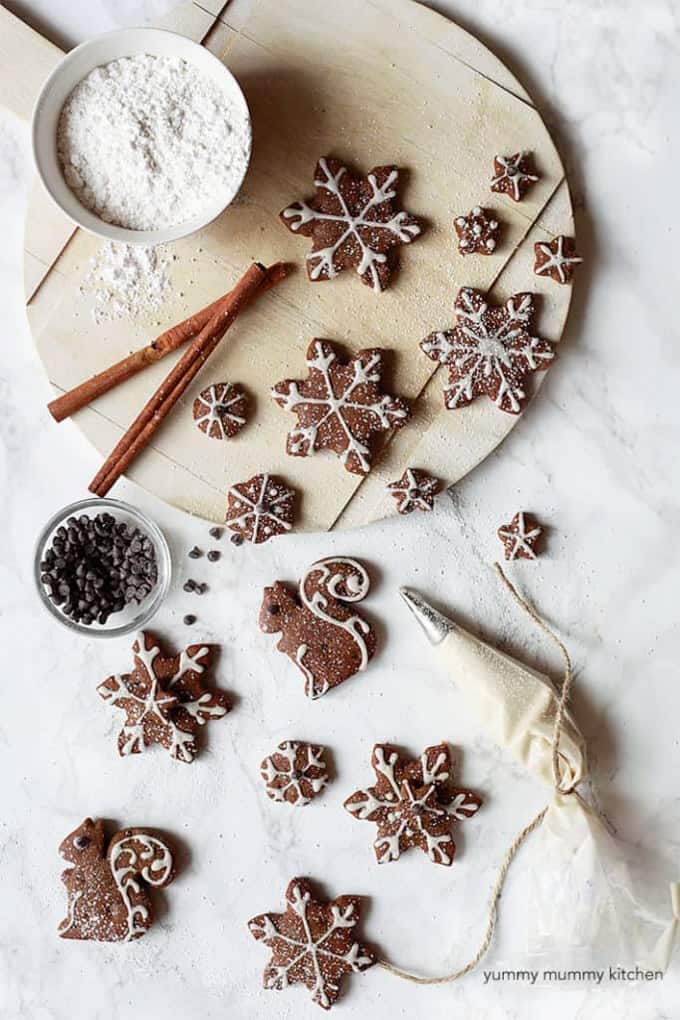 vegan gingerbread cookies in star and squirrel shape with icing on top and two cinnamon sticks, a bowl of powdered sugar, and chocolate chips on the side