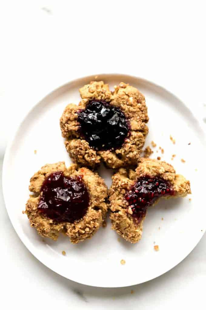 three thumbprint cookies on a white plate on a white surface with cookie crumbles on the side