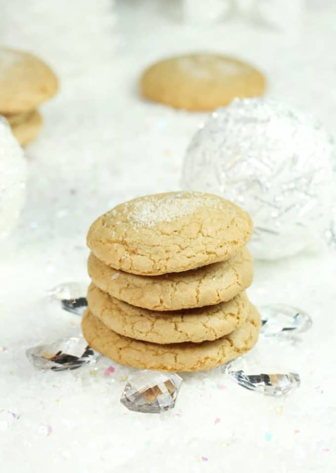 a stack of vegan sugar cookies on a white surface with more cookies and Christmas decoration in the background