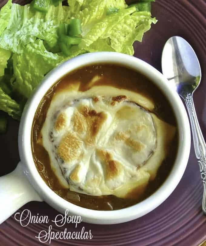 vegan French onion soup in a white bowl with lettuce in the background and a spoon on the side