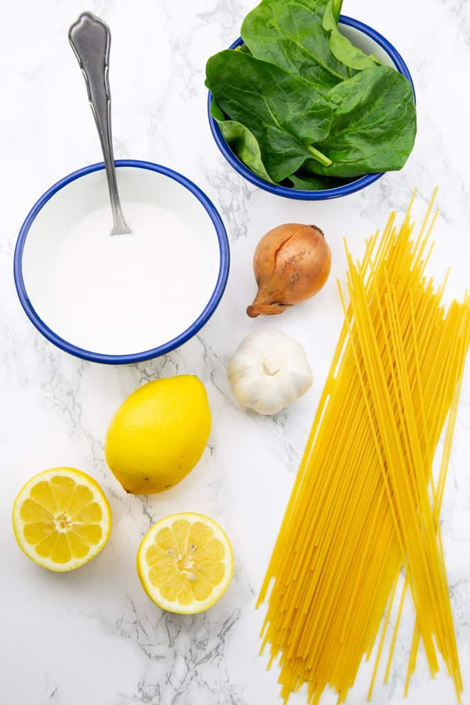 a bowl with coconut milk, a bowl with spinach, two lemons, garlic, an onion, and uncooked spaghetti on a marble countertop