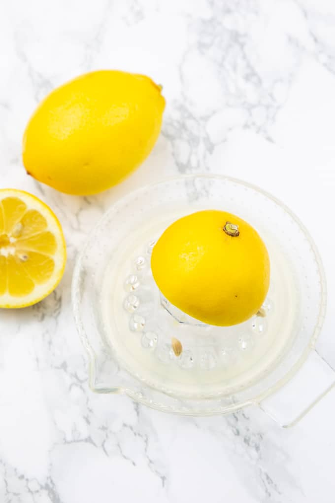 two lemons with a glass lemon squeezer on a marble countertop