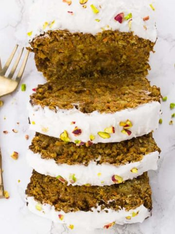three slices of vegan carrot cake on a marble countertop with two forks on the side