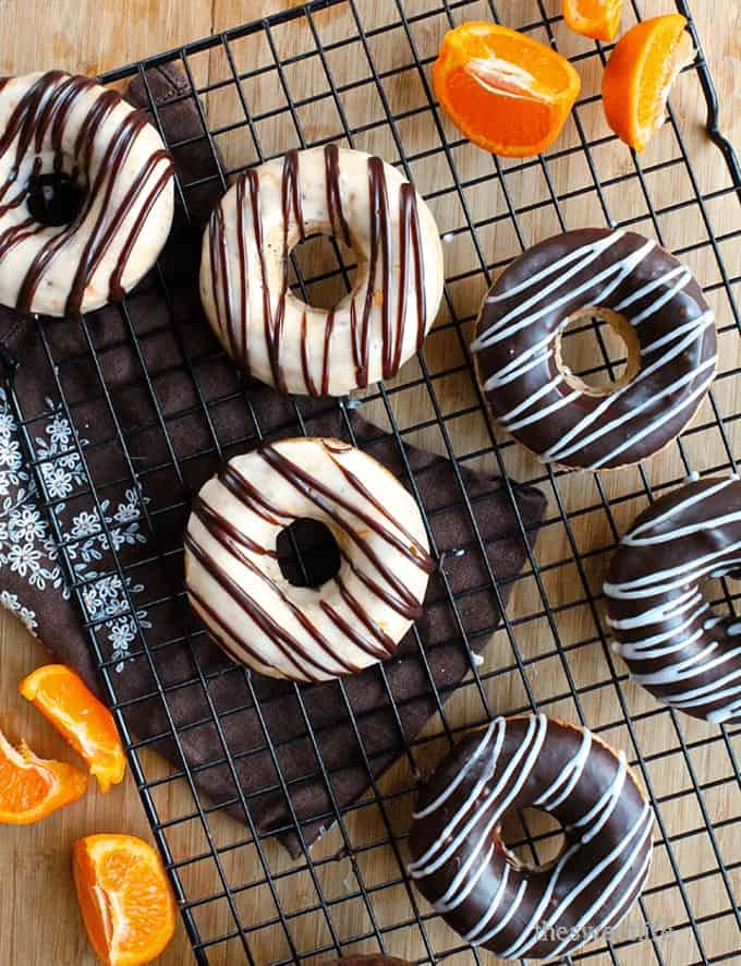 vegan orange donuts with chocolate glaze on a cooling rack with oranges on the side