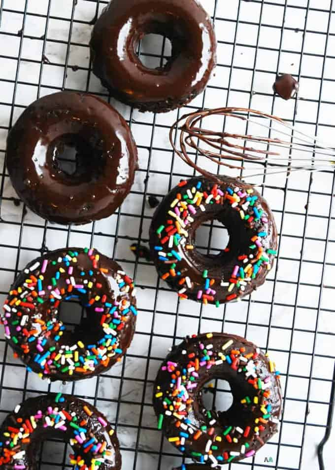 six vegan chocolate donuts on a cooling rack with a whisk on the side