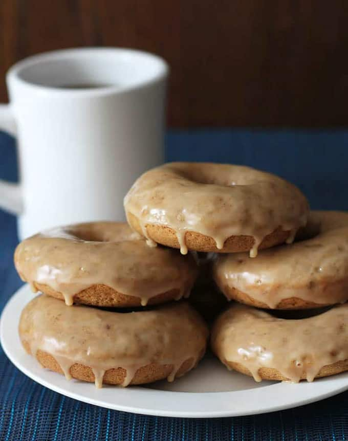 five vegan donuts on a white plate with a white mug in the background