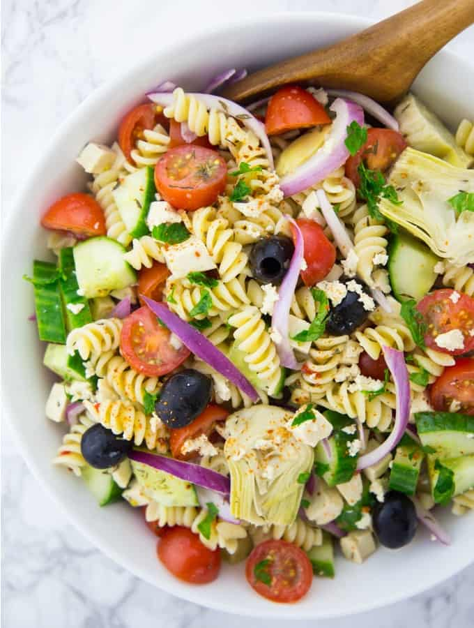 Greek pasta salad with red onions, cucumber, cherry tomatoes, olives, artichokes, and vegan feta cheese in a white bowl